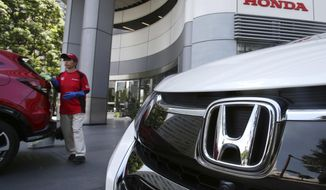FILE - In this July 31, 2018, file photo, an employee of Honda Motor Co. cleans a Honda car displayed at its headquarters in Tokyo. Japanese automaker Honda Motor Co. is reporting Tuesday, Oct. 30, 2018, a 21 percent jump in fiscal second quarter profit on cost cuts and healthy motorcycle sales. (AP Photo/Koji Sasahara, File)