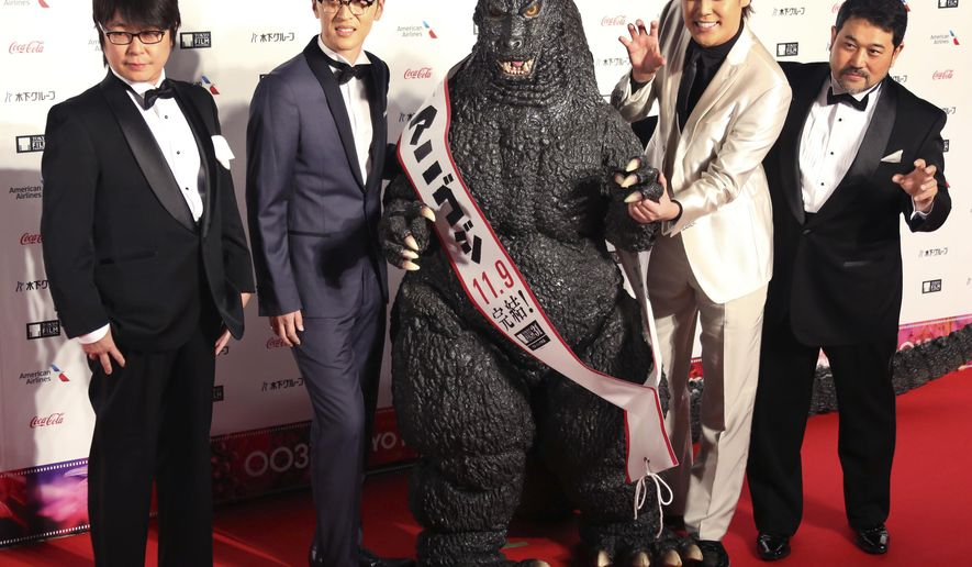 In this Thursday, Oct. 25, 2018, photo, film directors Hiroyuki Seshita, right, and Kobun Shizuno, left, pose with voice actors Mamoru Miyano, second from right, Takahiro Sakurai and Godzilla during the opening ceremony of the Tokyo International Film Festival in Tokyo. Godzilla is stomping back into theaters as a fire-breathing animated character, though the movie chosen to close this year's film festival is more focused on human drama than the monsters that have made the franchise famous. (AP Photo/Koji Sasahara)