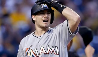 FILE - In this Friday, Sept. 7, 2018, file photo, Miami Marlins' J.T. Realmuto heads back to the dugout after striking out against the Pittsburgh Pirates in the first inning of a baseball game, in Pittsburgh. The agent for catcher J.T. Realmuto says his client has informed the Miami Marlins he won't sign a long-term contract, increasing the likelihood the team will trade yet another All-Star. (AP Photo/Keith Srakocic, File)