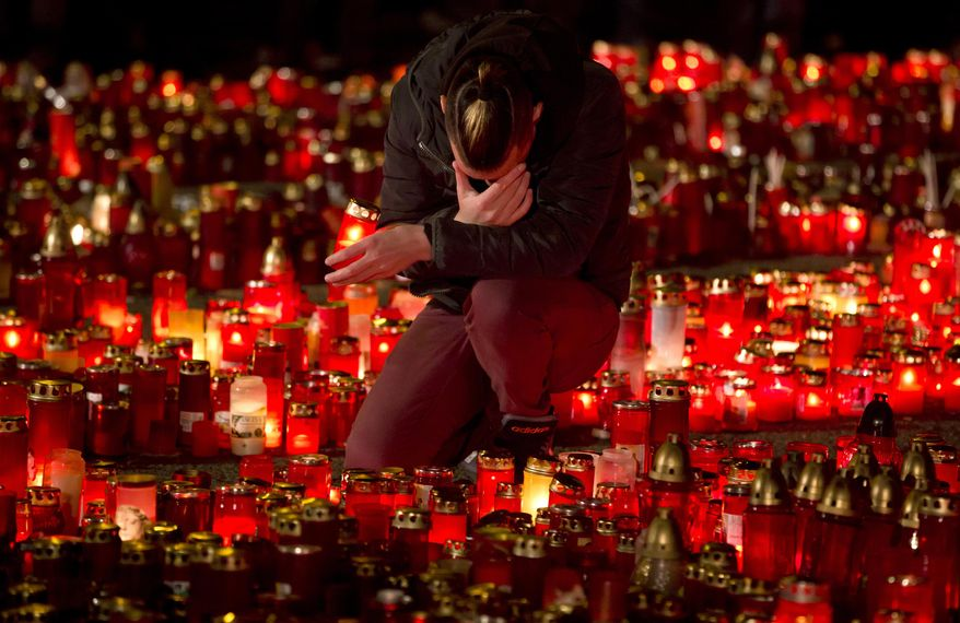 FILE - In this file photo dated  Friday, Nov. 6, 2015, a man reacts while holding a candle tribute outside the Colectiv nightclub in Bucharest, Romania, as people mark one week since a deadly fire started during a concert.  During ceremonies on Tuesday Oct. 30, 2018, the people of Romania marked three years since the deadly nightclub fire that killed 64 people.(AP Photo/Vadim Ghirda, file)