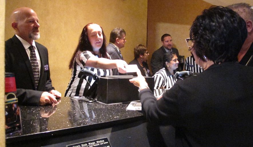 This Aug. 1, 2018 photo shows gamblers placing bets in the sports betting lounge at Harrah's casino in Atlantic City N.J. On Oct. 30, 2018, Caesars Entertainment, which owns Harrah's and two other Atlantic City casinos, announced a deal to open a sports lounge at Newark's Prudential Center aimed at hockey fans and concertgoers who can place sports bets over their mobile phones. (AP Photo/Wayne Parry)