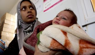 FILE - In this Feb. 14, 2017 file photo, a Syrian child from the informal Rukban camp for displaced Syrians, between the Jordan and Syria borders, receives treatment in a clinic run by UNICEF inside Jordan. Tens of thousands of Syrians stranded in a desert camp near the Jordanian border are at risk of malnutrition amid dwindling humanitarian supplies. The Rukban camp is home to some 45,000 people, many of them women and children, who are living in miserable conditions in the open desert area. A U.N. convoy was supposed to go in on Thursday, Oct. 25, 2018, but has now been indefinitely delayed. (AP Photo/Raad Adayleh, File)