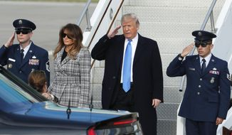 President Donald Trump, right, salutes as he departs Air Force One as he arrives with first lady Melania Trump on Tuesday, Oct. 30, 2018 in Coraopolis, Pa. The Trumps came to Pittsburgh honor the victims of the deadly shooting at a synagogue in Pittsburgh's Squirrel Hill neighborhood on Saturday. (AP Photo/Keith Srakocic)