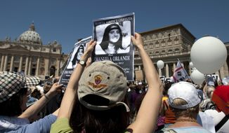 """FILE - In this May 27, 2012, file photo, demonstrators hold pictures of Emanuela Orlandi reading """"march for truth and justice for Emanuela"""" during Pope Benedict XVI's Regina Coeli prayer in St. Peter's square, at the Vatican. The Vatican says human bones were found during renovation work near its embassy to Italy, reviving speculation once again about the fate of Orlandi, the 15-year-old daughter of a Vatican employee who disappeared in 1983. (AP Photo/Andrew Medichini, File)"""
