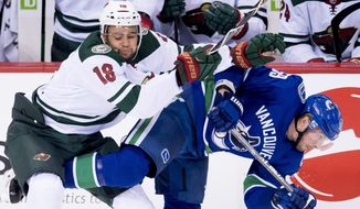 Minnesota Wild left wing Jordan Greenway (18) fights for control of the puck with Vancouver Canucks center Tim Schaller (59) during the second period of an NHL hockey game, Monday, Oct. 29, 2018, in Vancouver, British Columbia. (Jonathan Hayward/The Canadian Press via AP)
