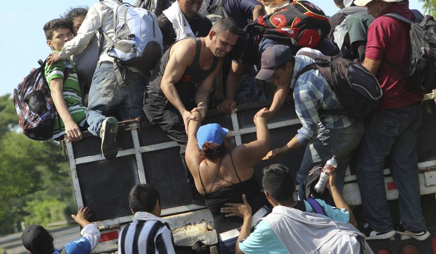 Migrants from El Salvador board a truck as they start on their way to the United States, from San Salvador, El Salvador, Wednesday, Oct. 31, 2018. A third group of migrants from El Salvador had already made it to Guatemala, and on Wednesday a fourth group of about 700 Salvadorans set out from the capital, San Salvador, with plans to walk to the U.S. border, 1,500 miles away. (AP Photo/Diana Ulloa)