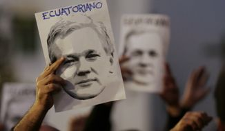 """People hold up images of Julian Assange that read in Spanish: """"Ecuadorian,"""" to show support for his double nationality, as they counter protest others demanding the government remove his Ecuadorean nationality outside the government palace in Quito, Ecuador, Wednesday, Oct. 31, 2018. Ecuador's government has provided the Australian hacker refuge for six years, but their relations have grown increasingly prickly as the years have dragged on with no solution in sight. (AP Photo/Dolores Ochoa)"""