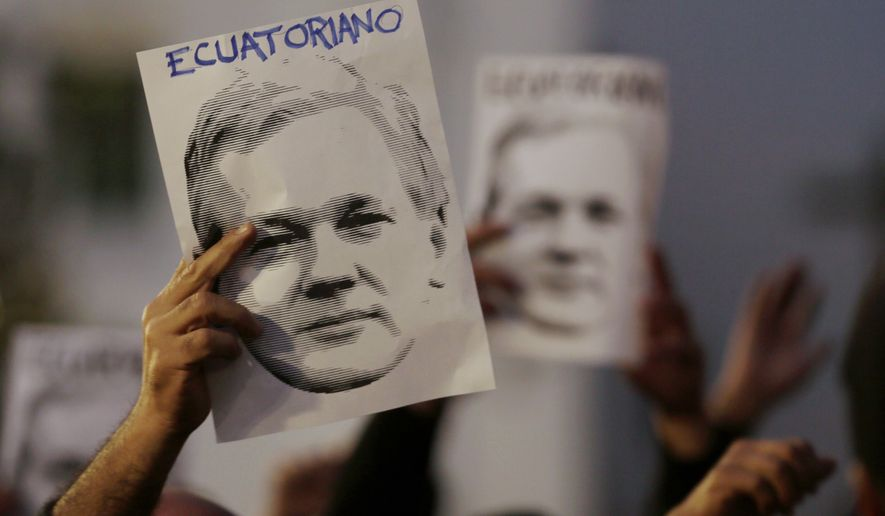"People hold up images of Julian Assange that read in Spanish: ""Ecuadorian,"" to show support for his double nationality, as they counter protest others demanding the government remove his Ecuadorean nationality outside the government palace in Quito, Ecuador, Wednesday, Oct. 31, 2018. Ecuador's government has provided the Australian hacker refuge for six years, but their relations have grown increasingly prickly as the years have dragged on with no solution in sight. (AP Photo/Dolores Ochoa)"