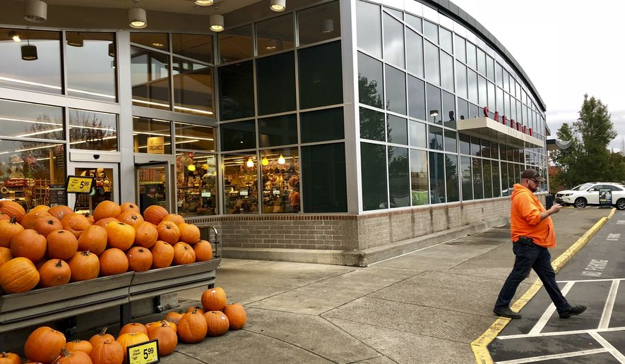 In this photo taken Wednesday, Oct. 31, 2018, in Lake Oswego, Ore., a shopper leaves a Safeway store. Grocery giant Albertsons/Safeway is one of several out-of-state grocery industry interests, including Costco, Kroger and the American Beverage Association, donating generously to a campaign for an Oregon ballot measure that would enshrine a ban on future grocery taxes in the state constitution. Opponents say the measure is an attempt to preempt a soda tax in the state. (AP Photo/Gillian Flaccus)