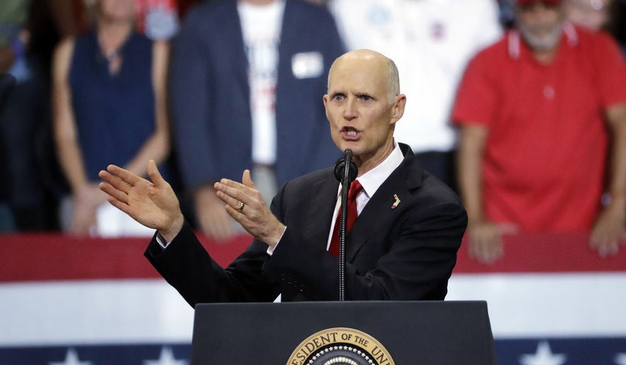 Florida Gov. Rick Scott gestures as he appears with President Donald Trump during a rally Wednesday, Oct. 31, 2018, in Estero, Fla. (AP Photo/Chris O'Meara) ** FILE **