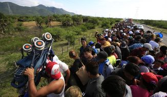 A man holds up a stroller as hundreds of migrants hitching a ride accommodate themselves on the back of truck, between Niltepec and Juchitan, Mexico, Tuesday, Oct. 30, 2018. The group is already significantly diminished from its estimated peak at over 7,000-strong. (AP Photo/Rebecca Blackwell)