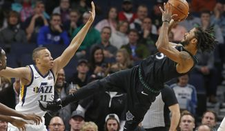 Minnesota Timberwolves' Derrick Rose, right, takes a fall-back shot as Utah Jazz's Dante Exum defends sueinf the first half of an NBA basketball game Wednesday, Oct. 31, 2018, in Minneapolis. (AP Photo/Jim Mone)