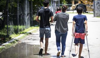 FILE - In this Sept. 4, 2018, file photo, refugees  are pictured on Nauru. Australia aims to remove all asylum seeker children from Nauru within two months as concerns escalate about their deteriorating health after languishing on the tiny Pacific atoll nation for up to five years. But cabinet ministers said on Thursday, Nov. 1,  the government is maintaining its much-criticized policy of sending all asylum seekers who attempt to reach Australia by boat to immigration camps on Nauru and Papua New Guinea. (Jason Oxenham/Pool Photo via AP, File)
