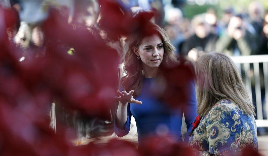 Britain's Kate, the Duchess of Cambridge, looks at a huge poppy installation as she arrives to visit IWM, the Imperial War Museum, to view letters relating to the three brothers of her great-grandmother, all of whom fought and died in the First World War, in London, Wednesday, Oct. 31, 2018. (AP Photo/Frank Augstein, pool)