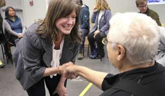 This Oct. 23, 2018 photos shows Alyse Galvin, an independent running for the U.S. House in Alaska, greeting Dwayne McKnight at a town hall meeting in Anchorage, Alaska. Galvin is challenging U.S. Rep. Don Young, who is the longest serving current member of the House, was first elected in 1973. (AP Photo/Mark Thiessen)