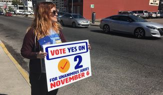 New Orleans resident Molly Ezell holds a sign promoting a Louisiana constitutional amendment that would require unanimous 12-member jury verdicts in serious felony cases in the state on Oct. 29, 2018 in New Orleans. Louisiana is one of only two states allowing convictions by jury votes of 10-2 or 11-1. The amendment that would change that is on the Nov. 6 ballot. (AP Photo/Kevin McGill)