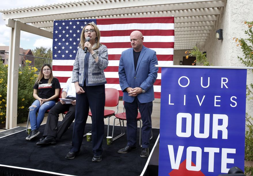 """In this Oct. 2, 2018 photo, former Rep. Gabby Giffords speaks as her husband, retired NASA astronaut and Navy Capt. Mark Kelly looks on as they kick off """"The Vote Save Lives"""" tour at UNLV in Las Vegas.  The 2018 election marks the first time that groups supporting gun control measures could spend more on a campaign than the National Rifle Association.  (Bizuayehu Tesfaye/Las Vegas Review-Journal via AP)/Las Vegas Review-Journal via AP)"""