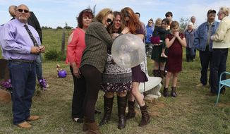 In this Oct. 21, 2018, photo, Sherri Pomeroy is embraced by her daugher-in-law, Chelsi Pomeroy, left, and her daughter, Kandi Pomeroy, right, as Sherri holds a balloon to release in honor of what would have been the 15th birthday for her slain daughter, Annabelle Pomeroy, in Sutherland Springs, Texas. Moments earlier, family and friends gathered with her at Annabelle's gravesite released balloons in different shades of purple, Annabelle's favorite color. At left is Annabelle's father, Frank Pomeroy. (Lisa Krantz/The San Antonio Express-News via AP)
