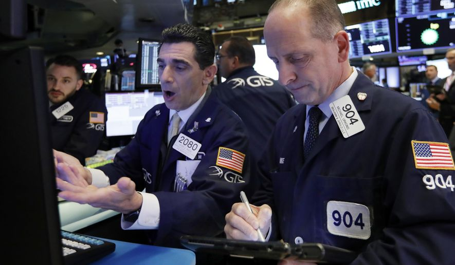FILE- In this Oct. 23, 2018, file photo specialist Peter Mazza, center, and trader Michael Urkonis work on the floor of the New York Stock Exchange. The U.S. stock market opens at 9:30 a.m. EDT on Wednesday, Oct. 31. (AP Photo/Richard Drew)