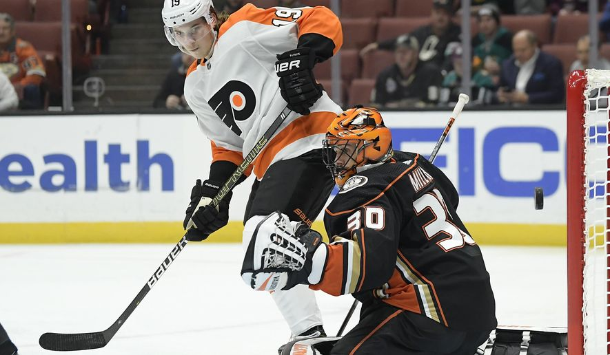 Anaheim Ducks goaltender Ryan Miller, right, is scored on by Philadelphia Flyers center Sean Couturier as center Nolan Patrick watches during the first period of an NHL hockey game Tuesday, Oct. 30, 2018, in Anaheim, Calif. (AP Photo/Mark J. Terrill)