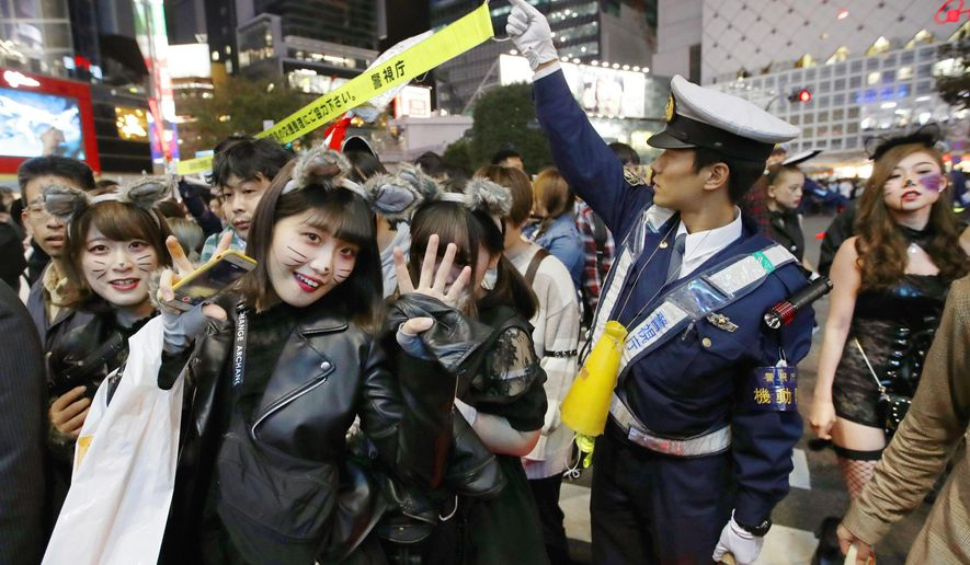 A police officer tries to control the traffic in downtown Tokyo on Halloween, Wednesday, Oct. 31, 2018. A fire broke out in a building in downtown Tokyo in an area crowded with Halloween celebrants, paralyzing traffic, but no one was reported injured. (Fumine Tsutabayashi/Kyodo News via AP)