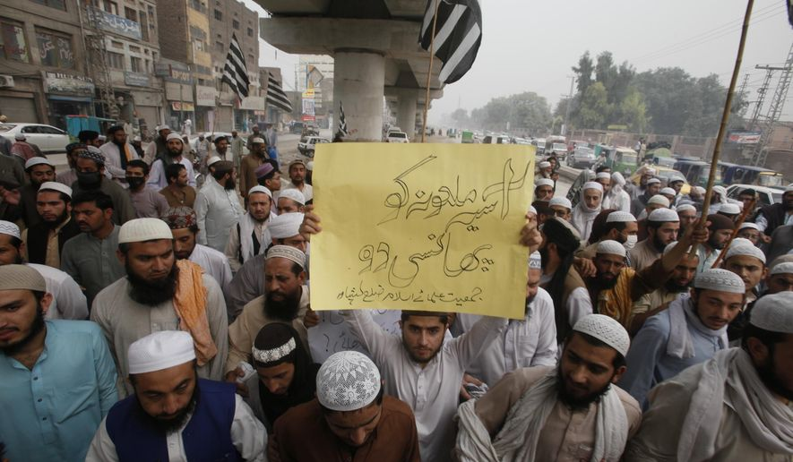 """Pakistan protesters rally to condemn a Supreme Court decision that ordered the release of Asia Bibi, a Catholic mother of five who has been on death row since 2010 accused of blasphemy, in Peshawar, Pakistan, Wednesday, Oct. 3, 2018. Pakistan's top court on Wednesday acquitted Bibi who was sentenced to death under the country's controversial blasphemy law, a landmark ruling that sparked protests by hard-line Islamists and raised fears of violence. Placard reads, """"hang blasphemous Asia."""" (AP Photo/Muhammad Sajjad)"""