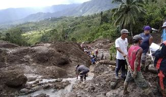 In this image provided by the Department of Public Works and Highways, Mountain Province District Engineering Office, rescuers dig through the earth to search for survivors after a massive landslide in Natonin township, Mountain Province in northern Philippines Wednesday, Oct. 31, 2018.  A massive landslide set off by a typhoon crashed down on two government buildings in a northern Philippine mountain province, officials said Wednesday.  (DPWH MPDSEO via AP)