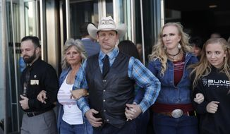 From left, Ryan Payne, Jeanette Finicum, widow of Robert LaVoy; Finicum, Ryan Bundy, Angela Bundy, wife of Ryan Bundy and Jamie Bundy, daughter of Ryan Bundy, walk out of a federal courthouse in Las Vegas. Ryan Bundy, the rancher's son who is campaigning for Nevada governor, is suing current and former U.S. government officials, alleging malicious prosecution after charges were dismissed against him in a 2014 armed standoff with federal land agents. (AP Photo/John Locher, File)