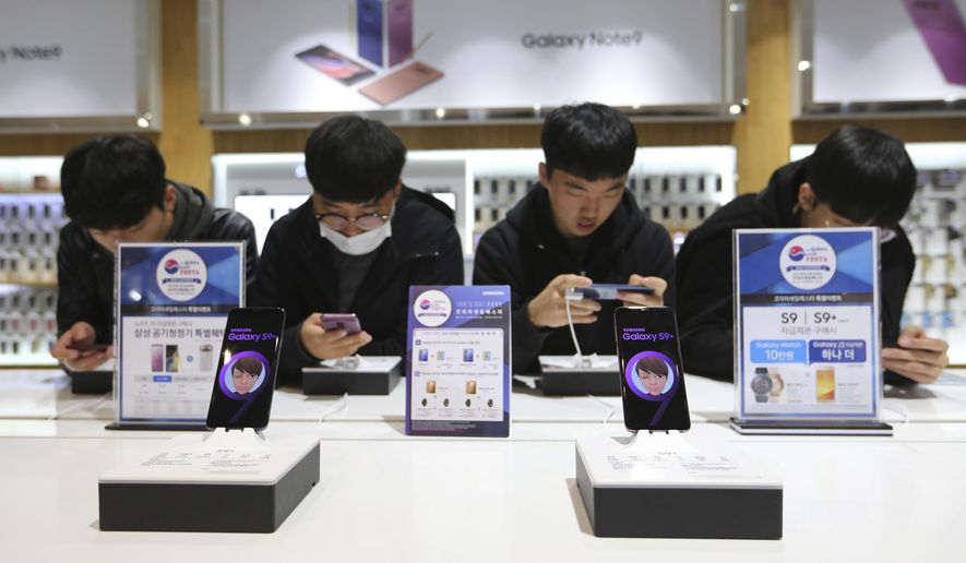 Middle school students try out Samsung Electronics' Galaxy S9+ smartphones at its shop in Seoul, South Korea, Wednesday, Oct. 31, 2018. Samsung Electronics Co. has posted record operating profit for the last quarter with robust demand for its mainstay memory chips compensating for a slowdown in its smartphone business. (AP Photo/Ahn Young-joon)