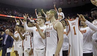 "FILE - In this Feb. 3, 2018, file photo, Texas players flash the ""Hook'em Horns"" sign and display a jersey of teammate Andrew Jones (1), who was diagnosed with leukemia, during the playing of the school song after defeating Oklahoma in an NCAA college basketball game, in Austin, Texas. Jones also was inspired by the outpouring of support that came in from Texas fans, Big 12 opponents and from across college basketball, after he was first diagnosed with leukemia and had to leave the team for treatment last season. (AP Photo/Michael Thomas, File)"