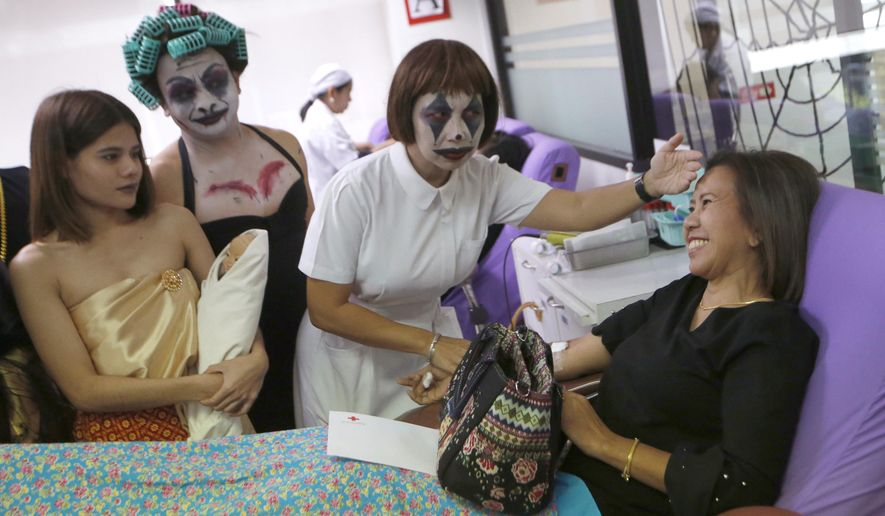 Thanat Chotrat, second from left, and Manful Bumroongton, third from left, dressed in a ghost costume for Halloween talk to volunteer donate blood on bed at the Thai Red Cross in Bangkok, Thailand, Thailand, Wednesday, Oct. 31, 2018. (AP Photo/Sakchai Lalit)