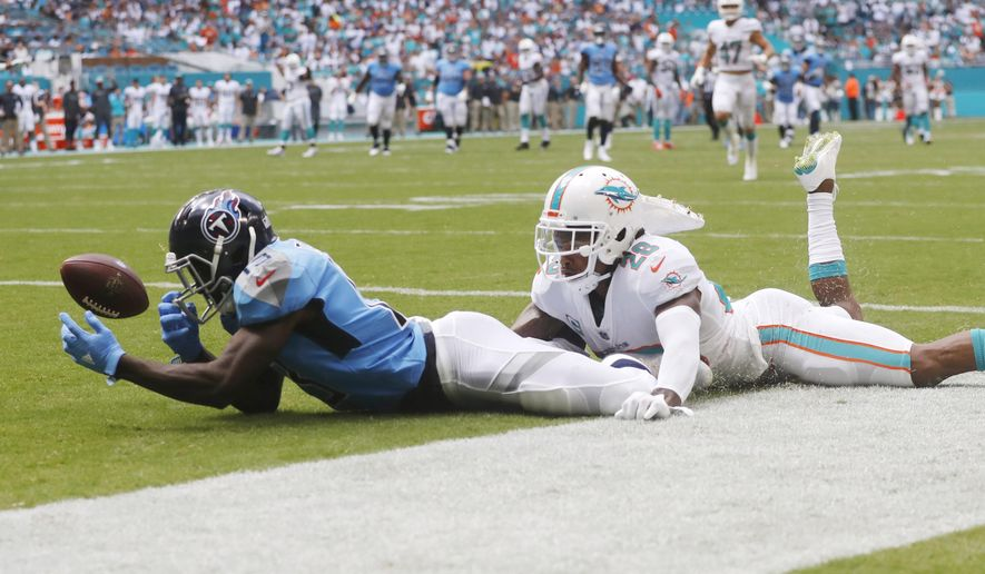 FILE - In this Sept. 9, 2018 file photo, Tennessee Titans wide receiver Taywan Taylor (13) drops a pass in the end zone as Miami Dolphins cornerback Bobby McCain (28) defends during the first half of an NFL football game, in Miami Gardens, Fla. The Tennessee Titans are doing their best to help a very young group of wide receivers grow up. General manager Jon Robinson's biggest personnel move before Tuesday's trade deadline was adding a fullback, not bolstering a receiving corps whose top trio includes a pair in their second seasons, Corey Davis and Taylor, and another Tajae Sharpe, essentially in his second season after sitting out 2017 on injured reserve. (AP Photo/Brynn Anderson, File)