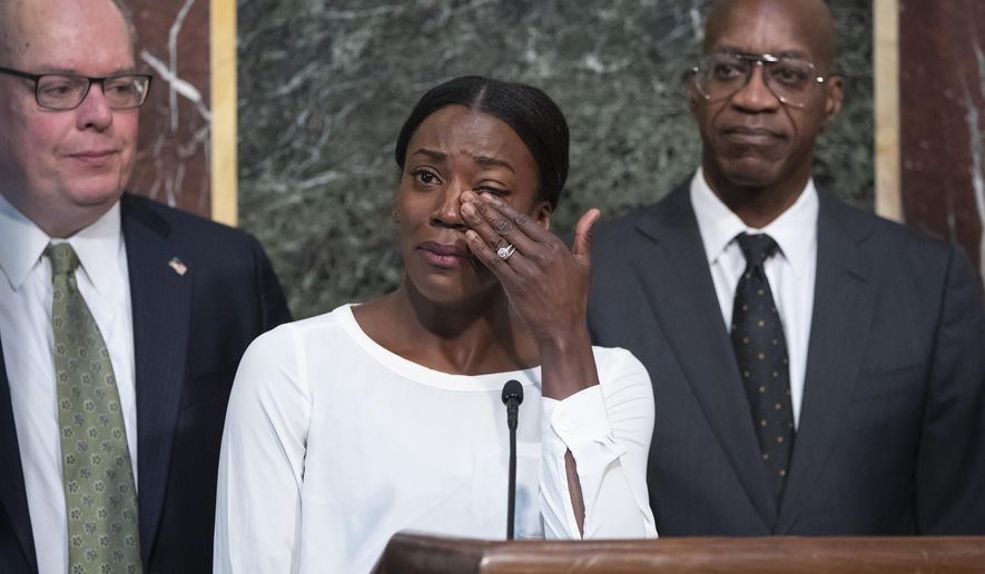 Alysia Montano, an American middle distance runner, flanked by Jim Carroll, deputy director of the Office of National Drug Control Policy, left, and Edwin Moses, chairman of the U.S. Anti-Doping Agency, wipes away tears as she recounts her experience at the 2012 Olympics when she finished behind two Russian runners using performance-enhancing drugs, during a White House event aimed at reforming the World Anti-Doping Agency, in Washington, Wednesday, Oct. 31, 2018. (AP Photo/J. Scott Applewhite)