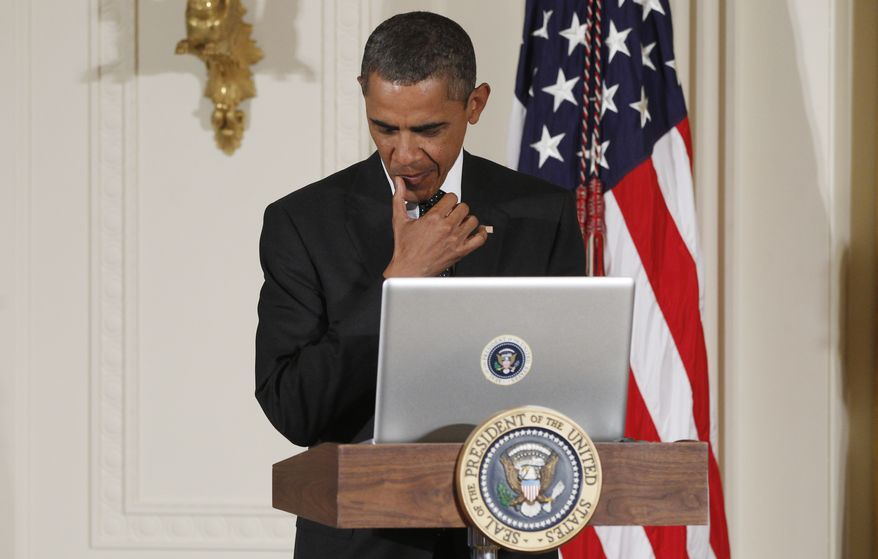 """President Barack Obama uses a laptop computer to send a tweet during a """"Twitter Town Hall"""" in the East Room of the White House in Washington, Wednesday, July 6, 2011. (AP Photo/Charles Dharapak) **FILE**"""