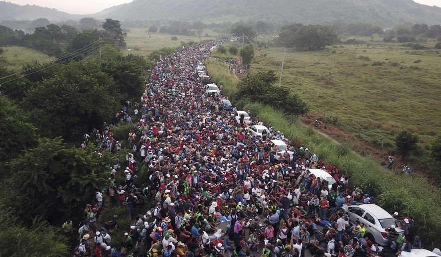 Members of a US-bound migrant caravan stand on a road after federal police briefly blocked their way outside the town of Arriaga, Saturday, Oct. 27, 2018. Hundreds of Mexican federal officers carrying plastic shields had blocked the caravan from advancing toward the United States, after several thousand of the migrants turned down the chance to apply for refugee status and obtain a Mexican offer of benefits. (AP Photo/Rodrigo Abd)