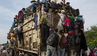 Members of a US-bound migrant caravan board a truck on their way north outside the town of Arriaga, Saturday, Oct. 27, 2018. Hundreds of Mexican federal officers carrying plastic shields had blocked the caravan from advancing toward the United States, after several thousand of the migrants turned down the chance to apply for refugee status and obtain a Mexican offer of benefits. (AP Photo/Rodrigo Abd)