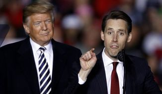 President Donald Trump listens as Republican Senate candidate Josh Hawley speaks during a campaign rally at Columbia Regional Airport, Thursday, Nov. 1, 2018, in Columbia, Mo. (AP Photo/Charlie Riedel)