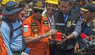 Chief of National Search and Rescue Agency Muhammad Syaugi, center, holds the flight data recorder from the crashed Lion Air jet during a press conference, onboard rescue ship anchored in the waters of Tanjung Karawang, Indonesia, Thursday, Nov. 1, 2018. Divers on Thursday recovered the flight data recorder from the Boeing 737 MAX 8 plane crashed early Monday on the seafloor, a crucial development in the investigation into what caused the 2-month-old plane to plunge into Indonesian seas earlier this week, killing all its passengers. (AP Photo/Fauzy Chaniago)