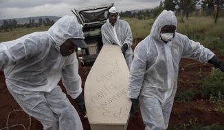 In this Thursday, April 12, 2018, file photo, mortuary workers carry the coffin of an unidentified man for burial at a cemetery outside Johannesburg. At least five bodies of unidentified people are buried on top of each other in each grave. (AP Photo/Bram Janssen)
