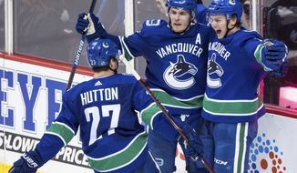 Vancouver Canucks' Jake Virtanen, right, celebrates his second goal against the Chicago Blackhawks with teammates Bo Horvat, back left, and Ben Hutton during the second period of an NHL hockey game Wednesday, Oct. 31, 2018, in Vancouver, British Columbia. (Darryl Dyck/The Canadian Press via AP)