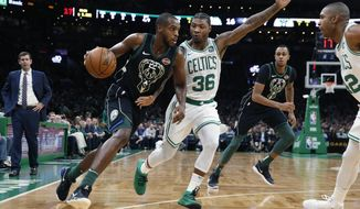Milwaukee Bucks' Khris Middleton (22) drives past Boston Celtics' Marcus Smart (36) during the first half of an NBA basketball game in Boston, Thursday, Nov. 1, 2018. (AP Photo/Michael Dwyer)
