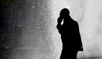 In this Thursday, Oct. 11, 2012, file photo, a pedestrian talking on a cellphone is silhouetted in front of a fountain in Philadelphia. Two U.S. government agencies are giving conflicting interpretations of a safety study on cellphone radiation: One says it causes cancer in rats. The other says there's no reason for people to worry. (AP Photo/Matt Rourke) ** FILE **