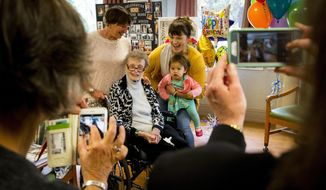 SallyLou Bonzer poses for a four-generation photo with her daughter, Lex Schmidt, left, granddaughter McKenzie Ma'aseia, a great-granddaughter Luisa Ma'aseia on the occasion of SallyLou's 100th birthday which was celebrated Wednesday, Oct. 24, 2018 by family and friends in Eugene, Ore. Bonzer, World War II veteran, landed on the beaches of Normandy, France three days after D-Day. (Andy Nelson/The Register-Guard via AP)