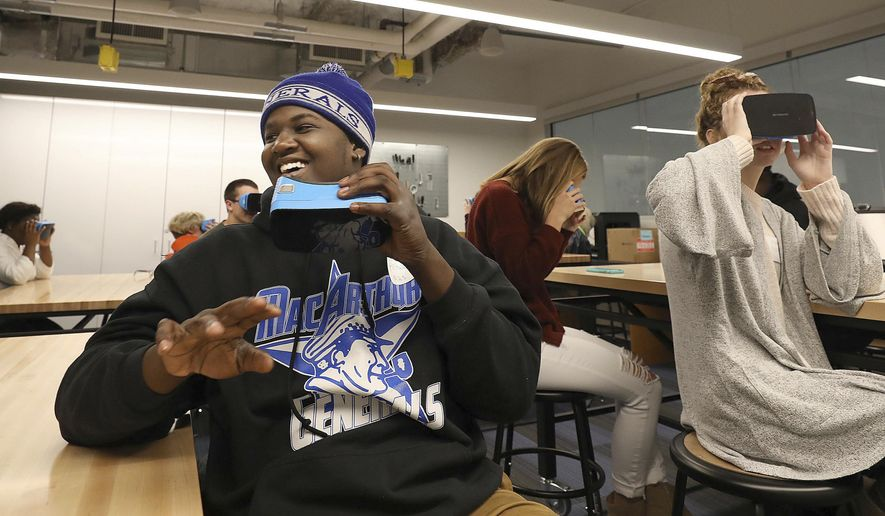 In this Oct. 13, 2018 photo, MacArthur High School student Antwone Brown reacts while taking  a virtual field trip through the solar system along with Rochester High School student Abbey Conner, middle, Peoria Christian High School student Madison Fisher, far right, and other students attending the Tomorrow's Teachers conference in the New Technologies Studio at Millikin University In Decatur, Ill. (Jim Bowling/Herald & Review via AP)/