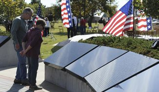 This photo taken Nov. 11, 2016, shows a couple looking at the names on the Cleveland County Veteran's Memorial during the Veterans Day and Memorial Ceremony, in Reavs Park in Norman, Okla.  (Kyle Phillips /The Norman Transcript via AP)