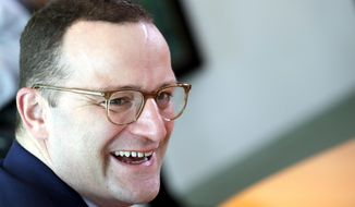 German Health Minister Jens Spahn laughs prior to the weekly cabinet meeting at the chancellery in Berlin, Germany, Wednesday, Oct. 31, 2018. (AP Photo/Michael Sohn)