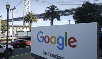 This photo shows signage outside the offices of Google in San Francisco with the San Francisco-Oakland Bay Bridge in the background, Wednesday, Oct. 31, 2018. Hundreds of Google employees are expected to temporality leave their jobs Thursday morning in a mass walkout protesting the internet company's lenient treatment of executives accused of sexual misconduct. The San Francisco office is one of the offices that the walkout will take place. (AP Photo/Michael Liedtke)