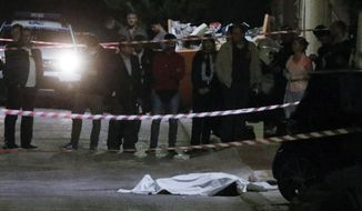 In this photo taken on Wednesday, Oct. 31, 2018, police officers stand over the covered body of Greek-Australian John Macris who was shot dead outside his house in southern Athens. Police are investigating the shooting death of a 46-year-old Greek-Australian who was gunned down outside his home in a seaside suburb of Athens. An autopsy on the body of John Macris was to be carried out Thursday. (Giorgos Kontarinis/Eurokinissi via AP)