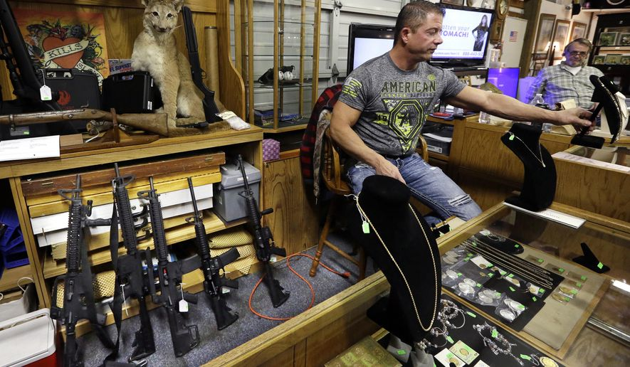 FILE - In this Oct. 20, 2017 file photo, Johnny's Auction House owner John West prepares items, including a line of assault rifles at left, for auction where the company handles gun sales for both civilians and a half dozen police departments and the Lewis County Sheriff's Office, in Rochester, Wash. The Spokane City Council is considering a proposal to prohibit the police department from selling forfeited firearms, following an Associated Press investigation that found that more than a dozen guns sold by law enforcement agencies in Washington state ended up in new police investigations. (AP Photo/Elaine Thompson, File)