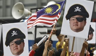 "FILE - In this April 14, 2018, file photo, protesters hold portraits of Jho Low illustrated as a pirate during a protest in Kuala Lumpur, Malaysia. The United States Justice Department on Thursday charged the fugitive Malaysian financier in a money laundering and bribery scheme that pilfered billions of dollars from a Malaysian investment fund created to promote economic development projects in that country. The three-count indictment charges Low Taek Jho, who is also known as Jho Low, with misappropriating money from the state-owned fund and using it for bribes and kickbacks to foreign officials, to pay for luxury real estate, art and jewelry in the United States and to fund Hollywood movies, including ""The Wolf of Wall Street."" (AP Photo/Sadiq Asyraf, File)"